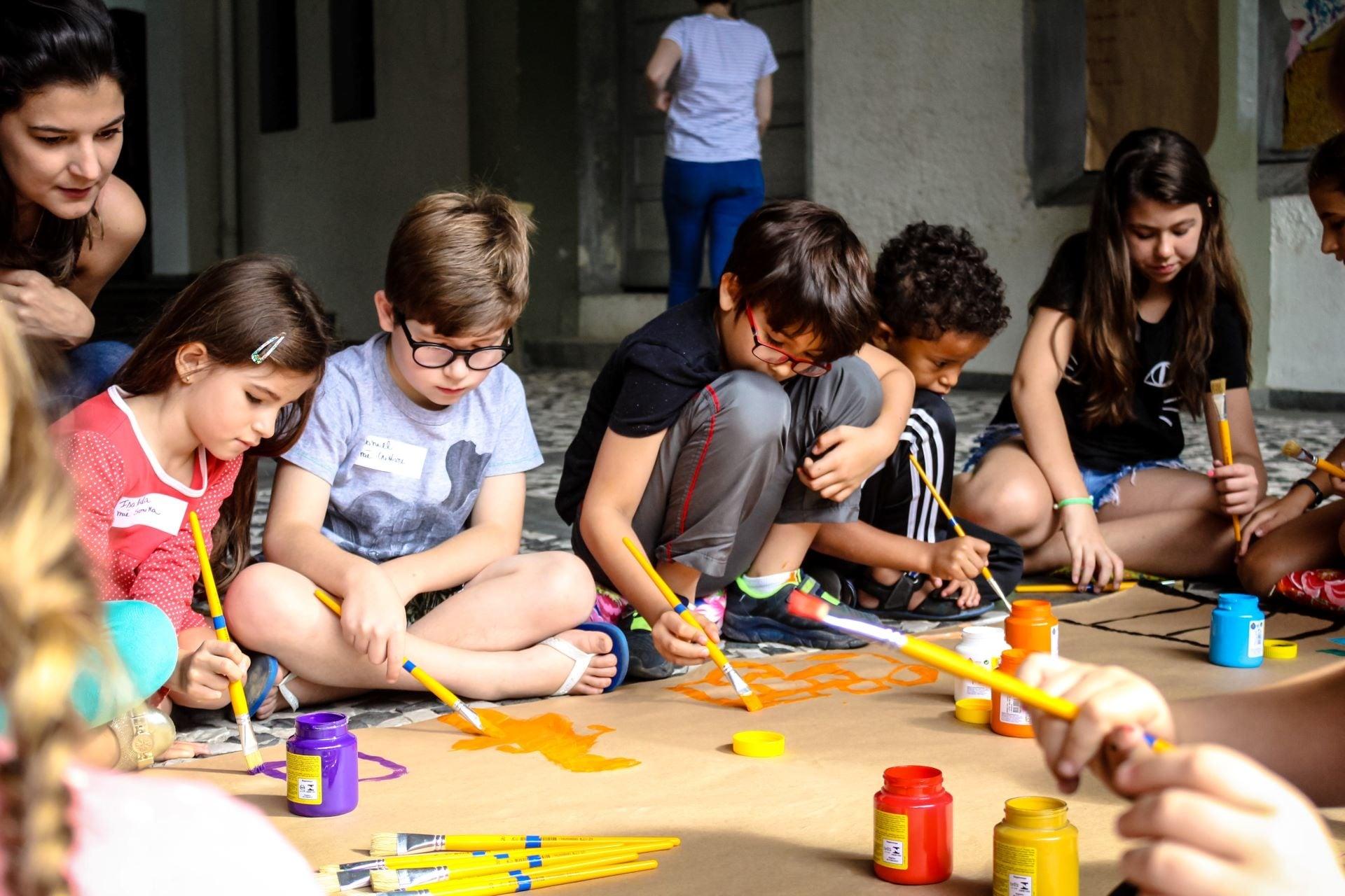 Crianças pintando um papel craft a partir da história de um áudio livro.