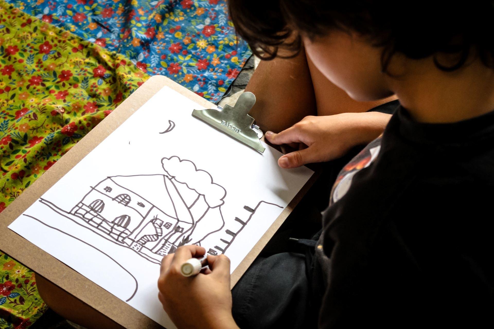Criança desenhando a sua casa em uma prancheta