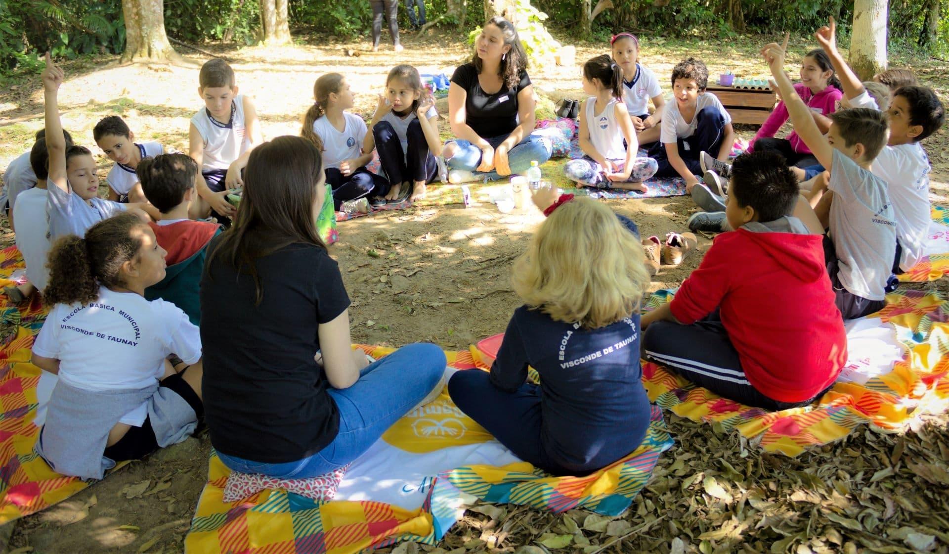 Crianças sentadas em roda, ao ar livre, aprendendo sobre meio ambiente e sustentabilidade.