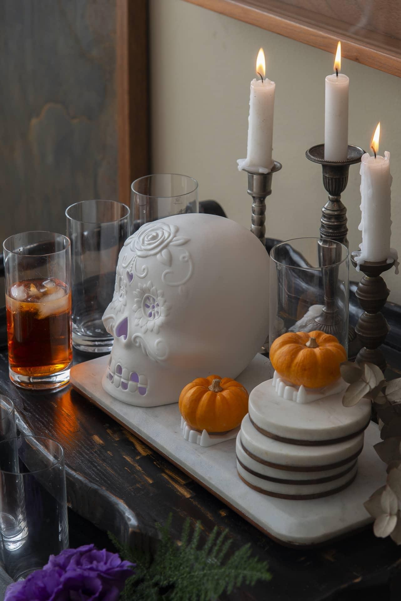 Caveira estilizada, branca e lilás, aparece cercada por quatro copos, duas abóboras miniatura, e três castiças com velas brancas.