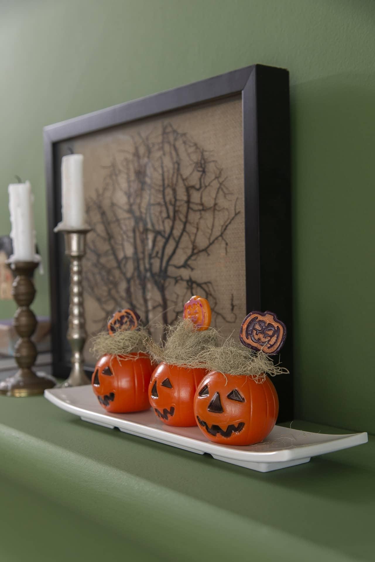 Travessa retangular com enfeites de Halloween e pirulitos em forma de abóbora.