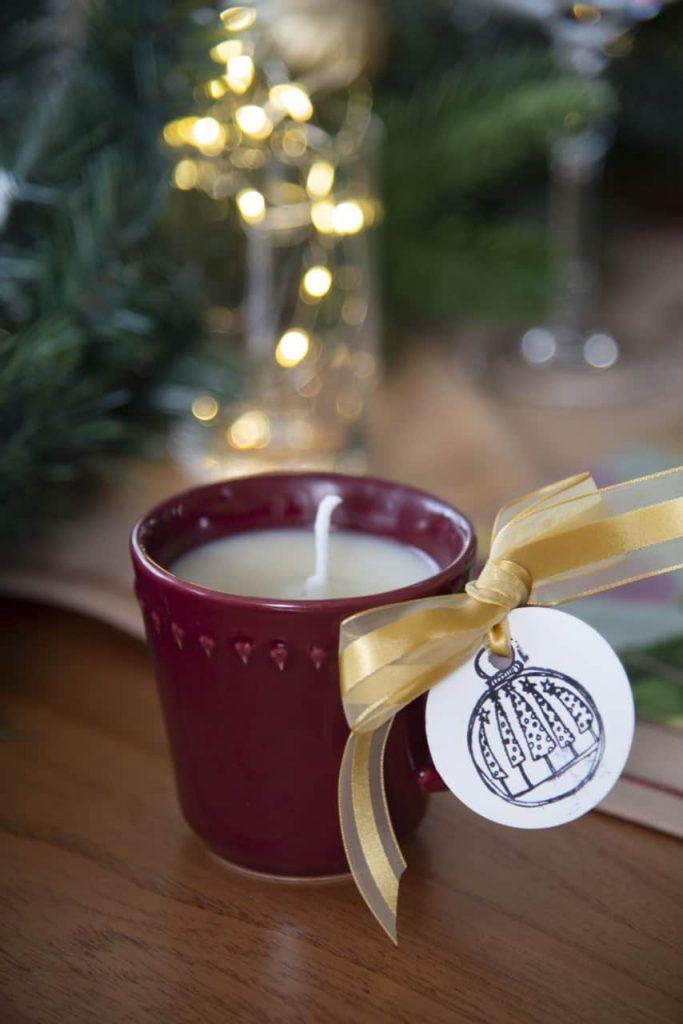Detalhe da mesa posta de Natal: vela feita dentro da xícara de porcelana vinho.