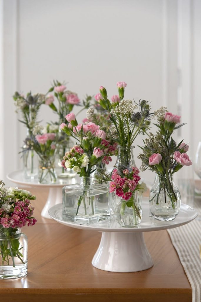 Várias garrafas com flores sobre um prato de bolo, branco, com pé.
