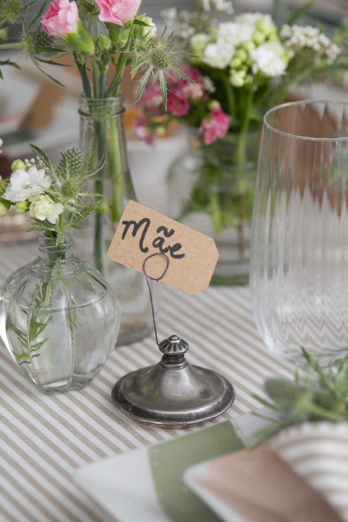 """Foto aproximada com o marcador de lugar na mesa exibindo a etiqueta com a palavra """"mãe""""."""
