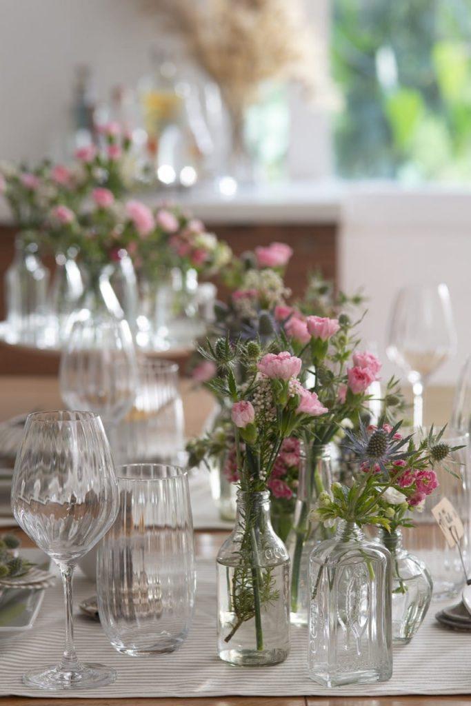 Taças, copos e garrafas com flores.