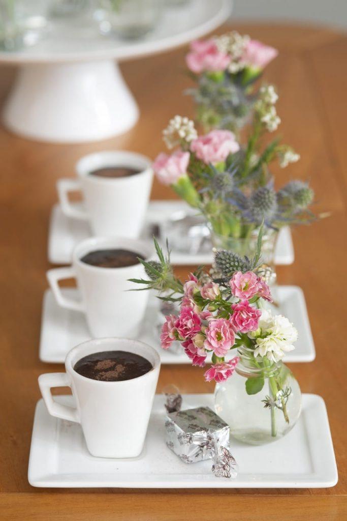 Três xícaras sobre pires retangulares, ambos de porcelana branca. Sobre cada pires há uma xícara, um bombom e um vasinho com flores.