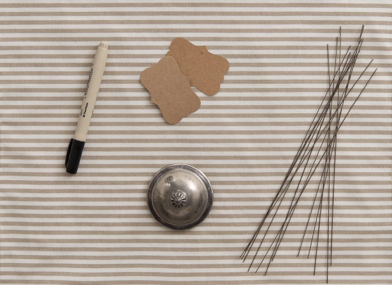 Foto feita de cima mostra uma caneta, duas etiquetas de papel, uma tampa de açucareiro de metal, e vários pedaços de arame