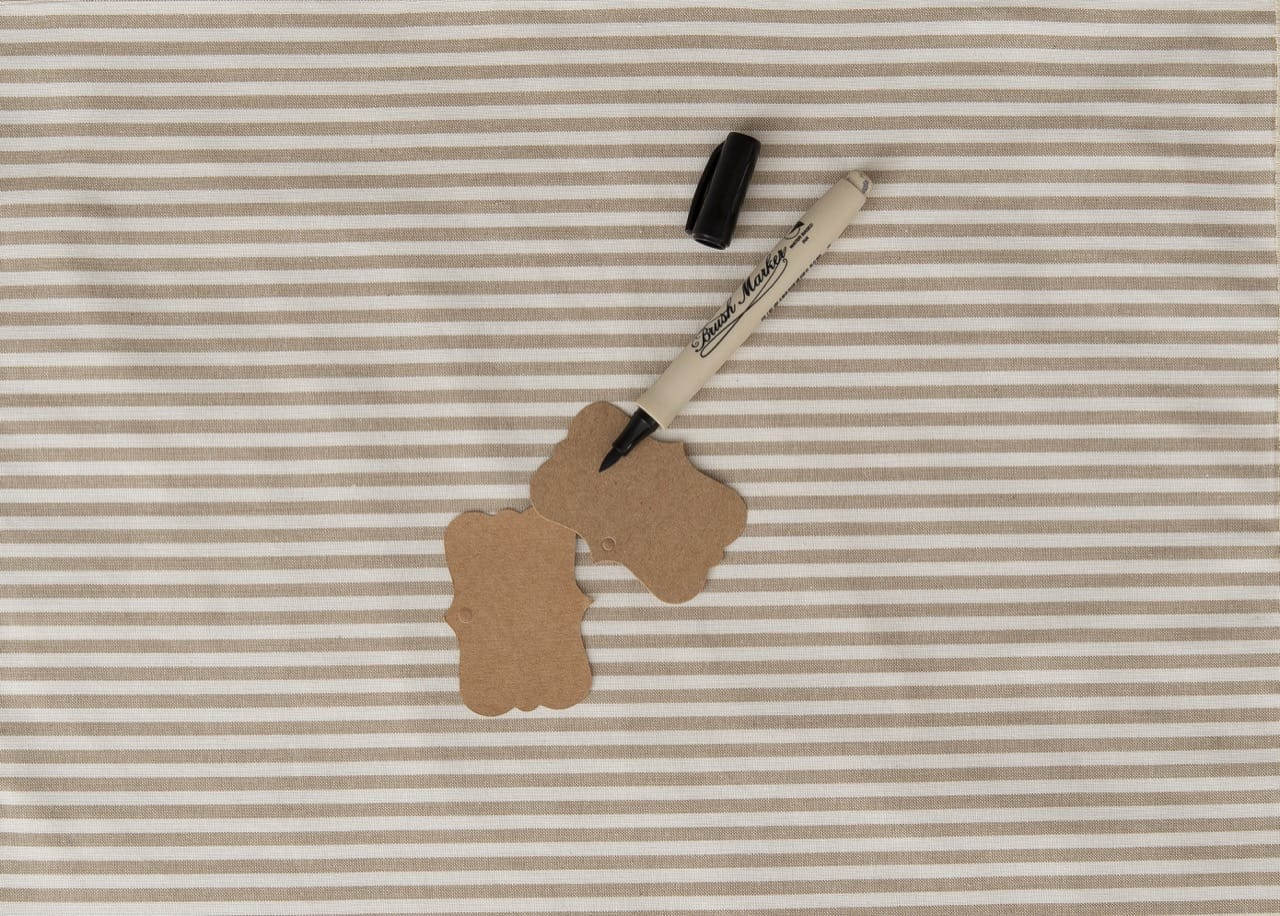 Duas etiquetas de papael e uma caneta preta de ponta porosa