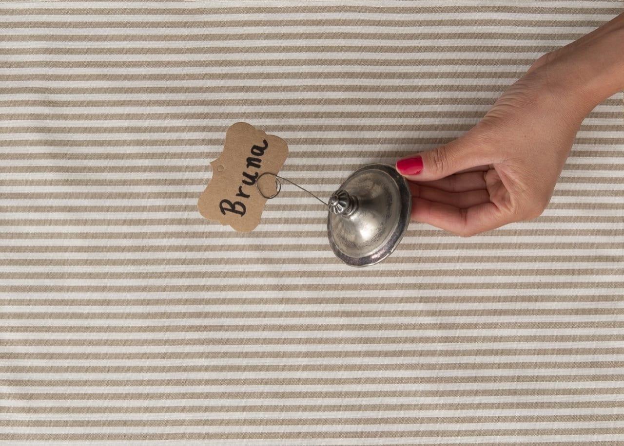 Mão feminina segura a tampa do açucareiro com a etiqueta de papel já posicionada no arame, com o nome Bruna.