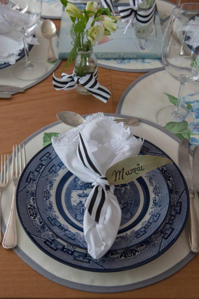O lugar da convidada de honra é sinalizado com uma folha manuscrita, presa ao guardanapo por uma fita listrada. Repare que há fitas, também, nos vidros que contêm ramalhetes de flores brancas.