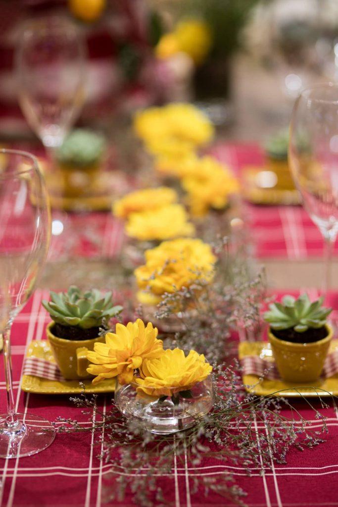 No centro da mesa, margaridas amarelas e galhos de Cáspia aparecem dentro de tigelas de vidro. As suculentas, por sua vez, ocupam as xícaras de cafezinho.
