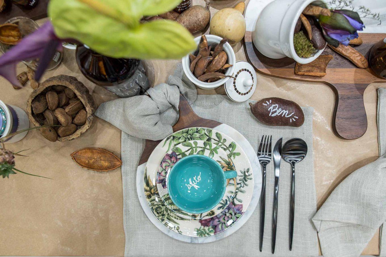 O guardanapo de linho cinza aparece amarrado na alça da tábua de madeira e mármore da Oxford. Dentro da xícara e em algumas sementes, há palavras amorosas e nomes de pessoas da família.
