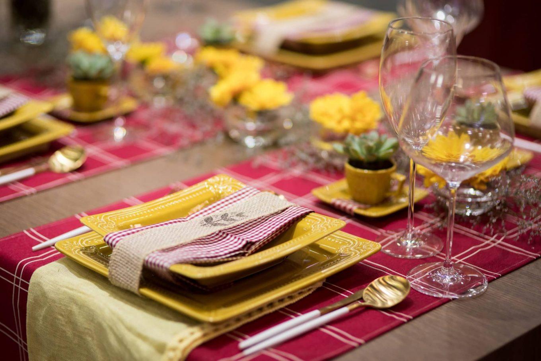 O xadrez vermelho e branco, presente nos caminhos de mesa e guardanapos, deixa a mesa com um ar campestre. Uma fita de juta, com um carimbo personalizado, abraça cada conjunto de pratos. Há, ainda um pano de prato amarelo embaixo deles, para criar mais um ponto de cor.