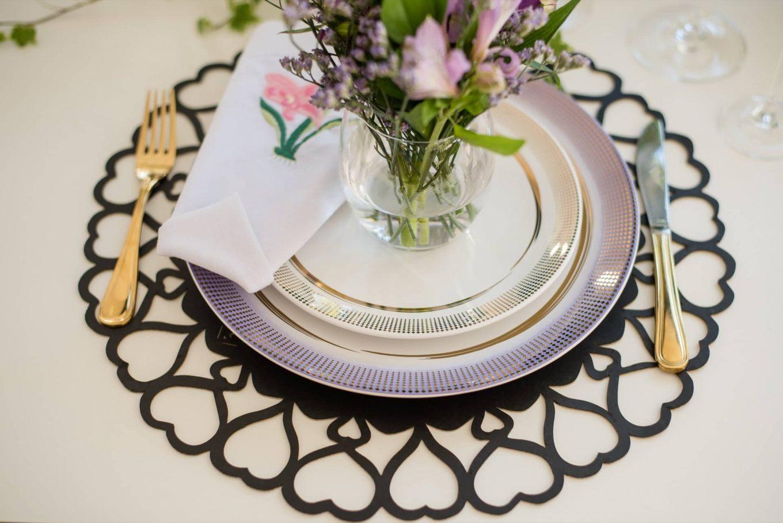 Adivinha quem vai ocupar o lugar na mesa que tem um jogo americano de corações, um lindo arranjo de flores e um guardanapo de linho com bordado do Ateliê da Mesa?