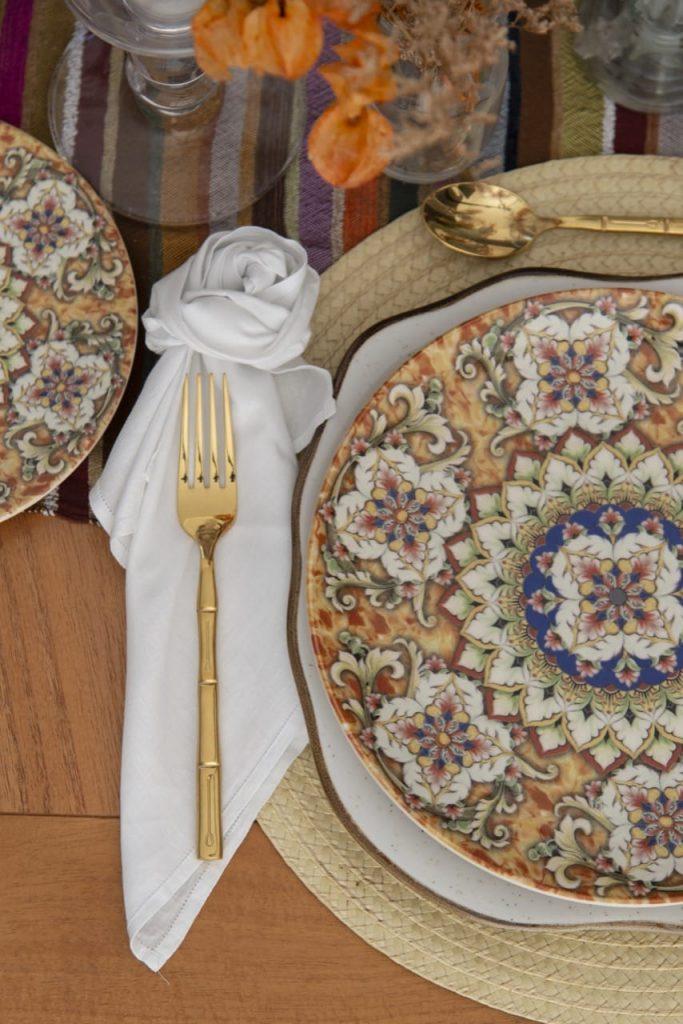 Foto feita de cima mostra prato estampado em tons de bege, laranja e azul; prato branco, guardanapo branco e talher dourado.