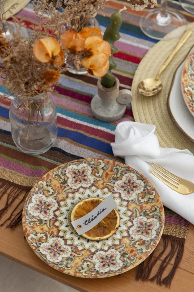 Marcadores de lugar personalizados dão charme extra ao almoço marroquino. Pires com rodela de laranja seca e etiqueta personalizada