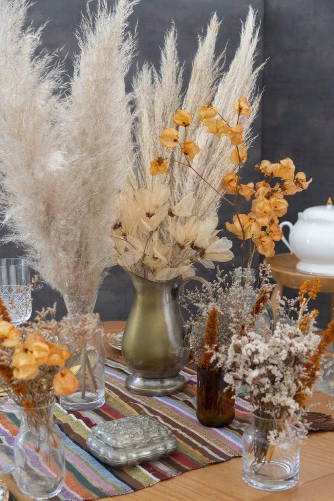 Jarra antiga de metal e vasos de vidro de tamanhos variados, com flores secas em tons de laranja, bege e branco. As cores remetem às paisagens do Marrocos