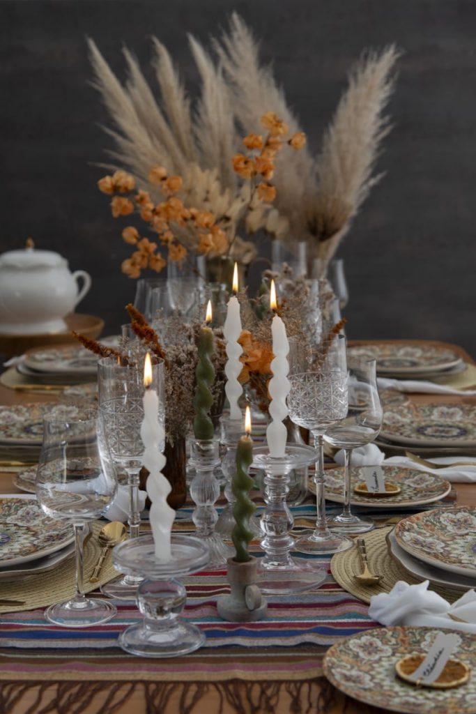 No centro da mesa de almoço marroquino, velas brancas torcidas e flores secas, criam um clima acolhedor.