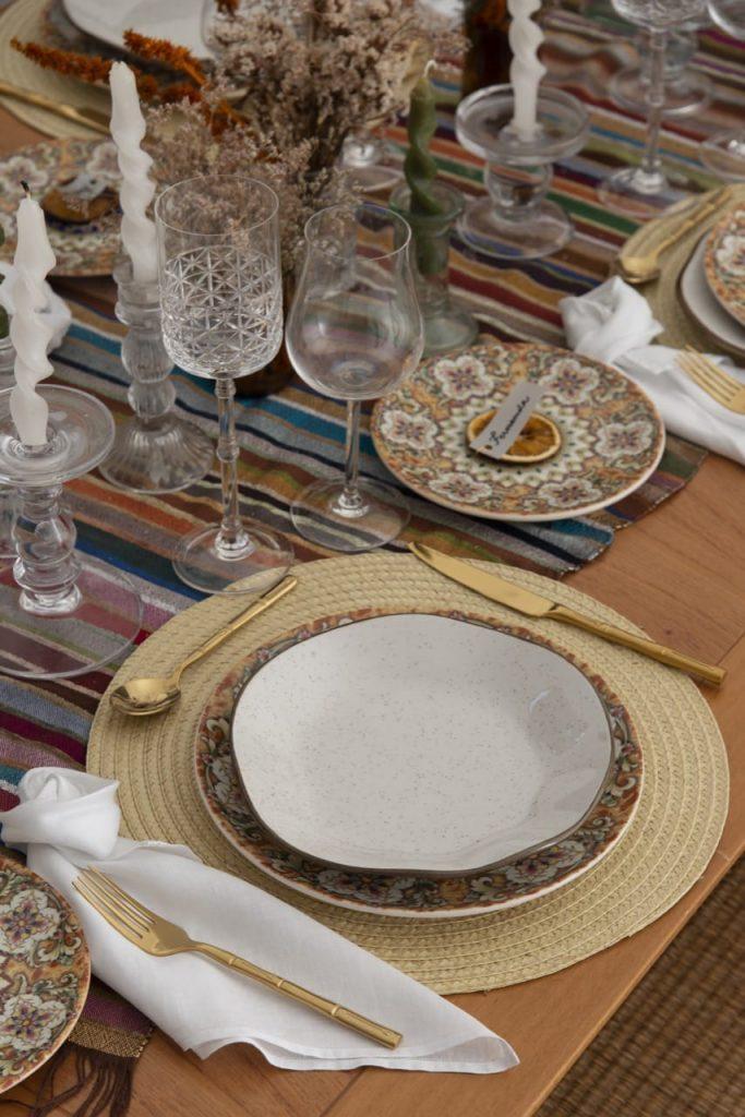 Um lugar na mesa posta para o almoço marroquino, com porcelanas finas e taças de cristal