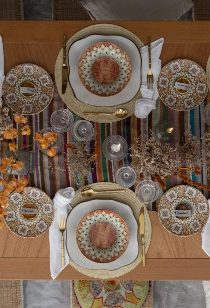Foto feita de cima mostra dois lugares na mesa posta com louças estampadas em cores terrosas