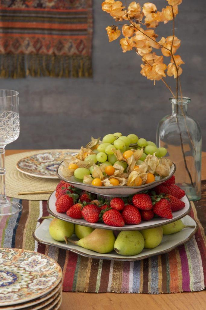 Prato de três andares com pêras, morangos, uvas e physalis (camapu).