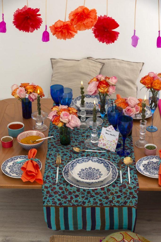 Dois lugares da mesa posta, com louças em azul e branco, copos com buquês de rosas e velas acesas.