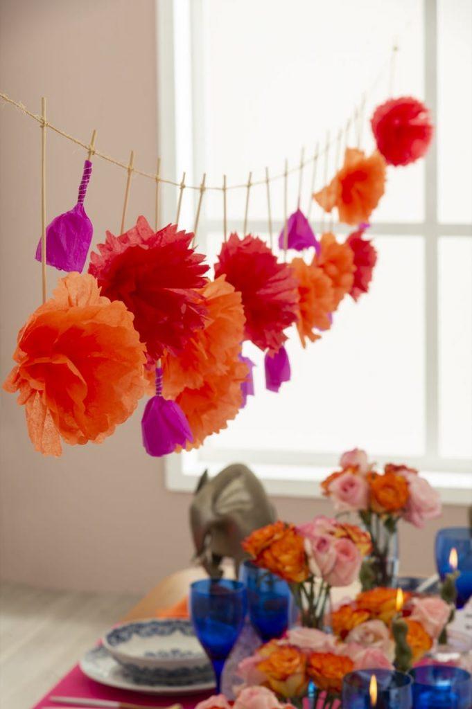 Varal com flores de papel em tons de laranja, vermelho e pink.
