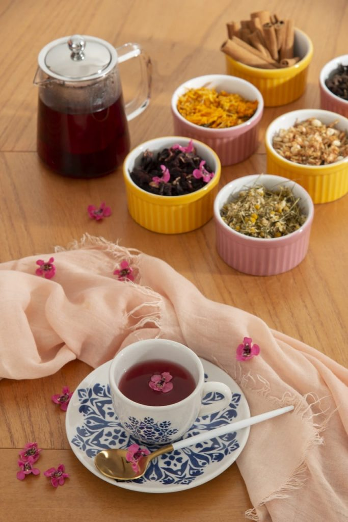 Uma xícara de chá, uma jarra de vidro e poter com vários tipos de chá
