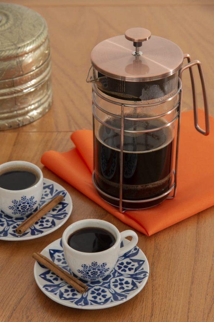 Cafeteira de vidro e duas xícaras de cafezinho. No pires, pedaços de canela em pau.