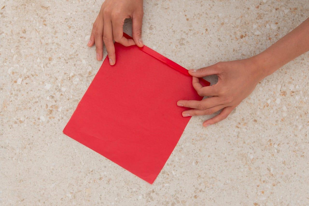 Duas mãos fazem uma dobradura no papel