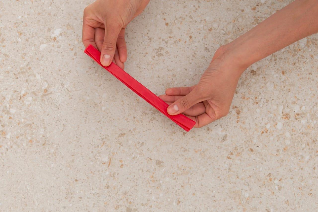 Duas mãos seguram o papel juntado todas as dobraduras da sanfona