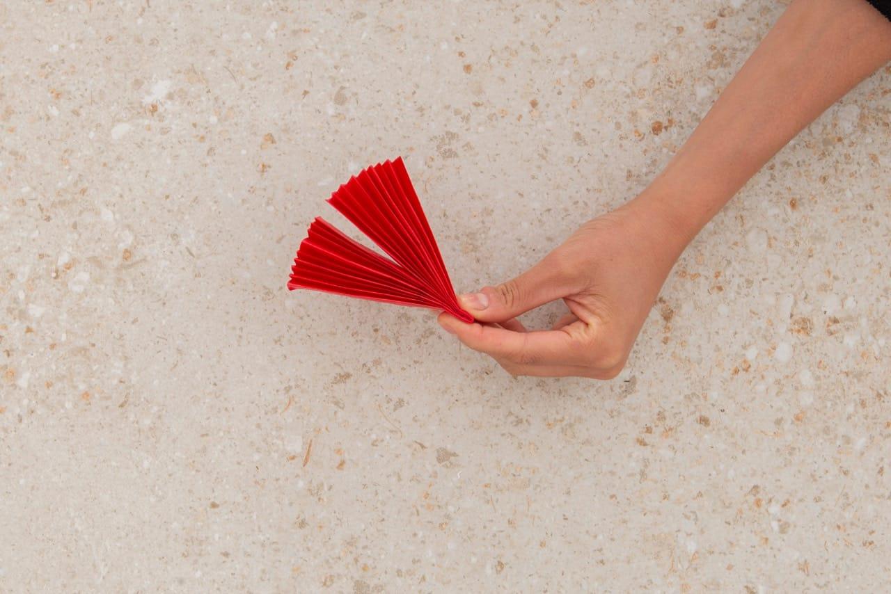 A sanfona que vai ser usado na flor de papel é dobrada ao meio
