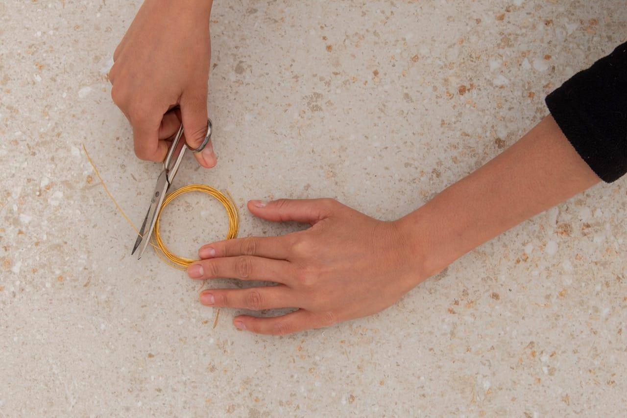 Duas mãos mostram o arame sendo cortado com a tesoura