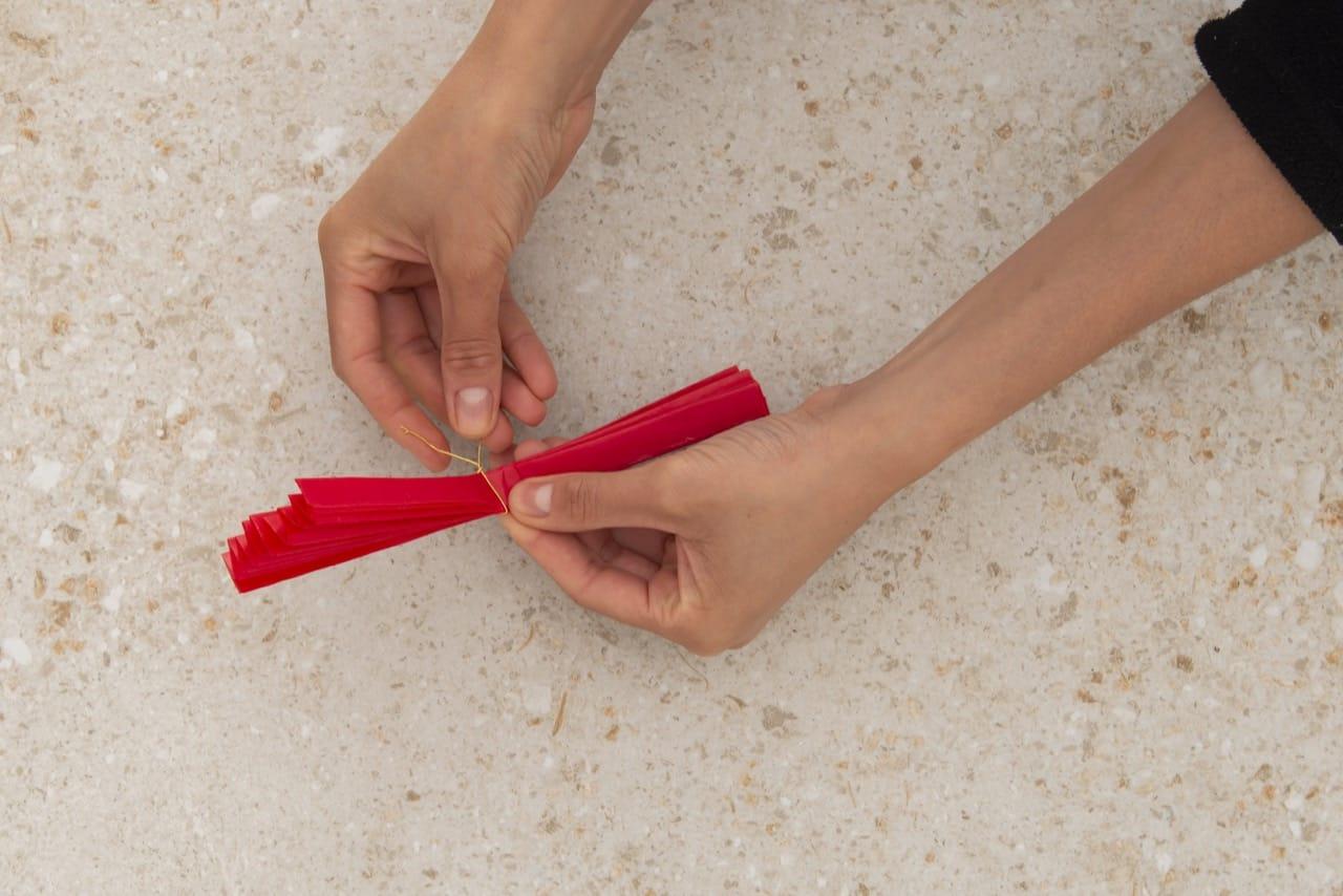 A sanfona de papel é amarrada com o arame.