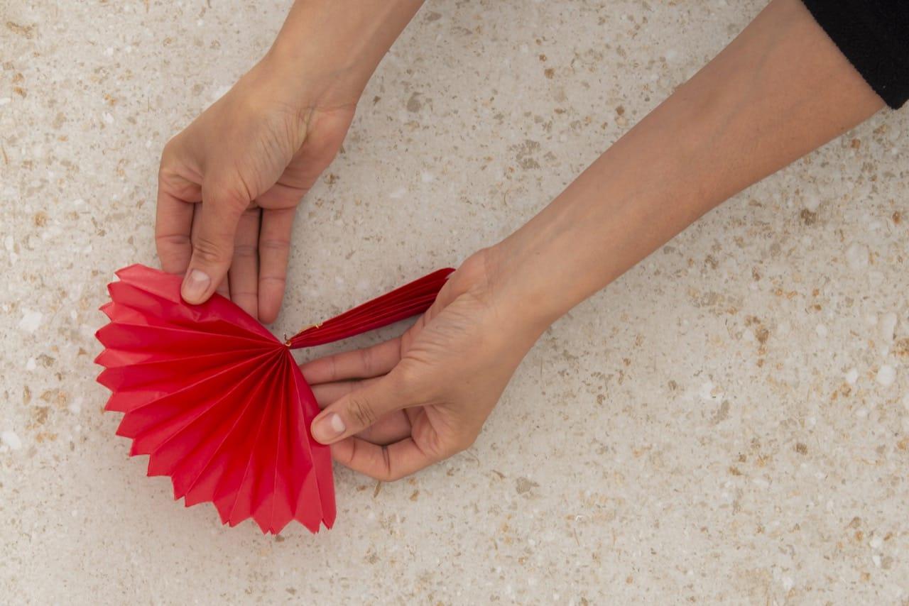 Duas mãos abrindo o papel de seda nas duas extremidades, em formato de leque.