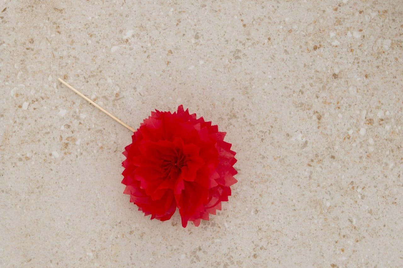 Flor de papel fixada no palito de madeira.