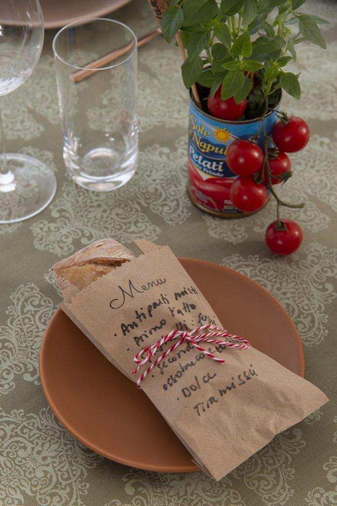 Pão tipo ciabatta dentro de um saquinho de papel pardo, com o menu do almoço italiano escrito a mão