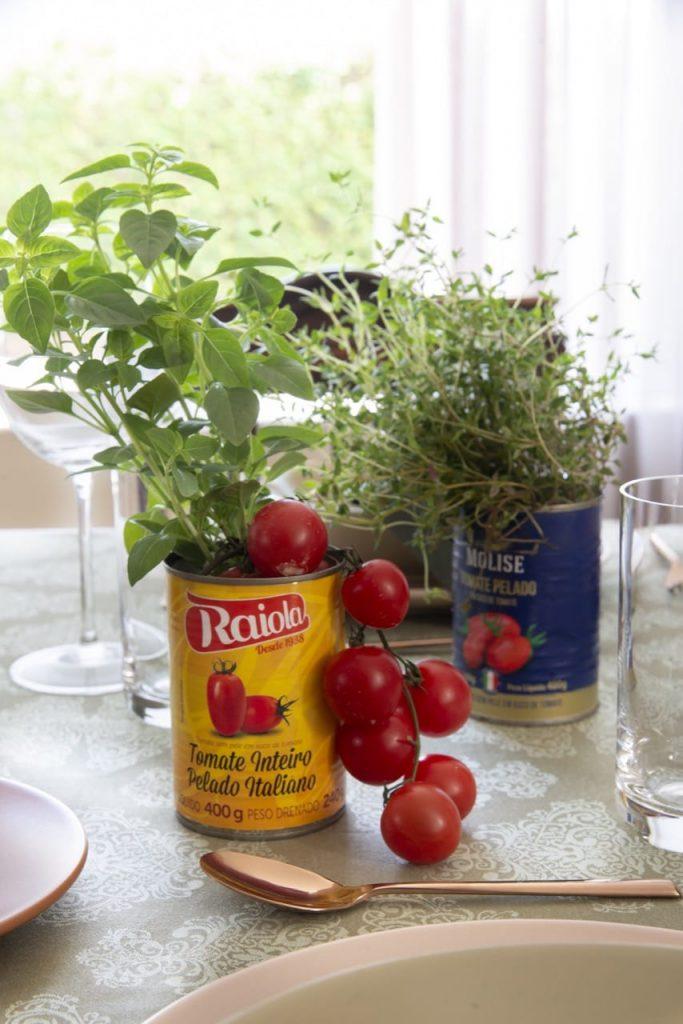 Duas latas de tomate pelado, uma com rótulo amarelo e outra com rótulo azul, contemdo ervas e tomates em rama.