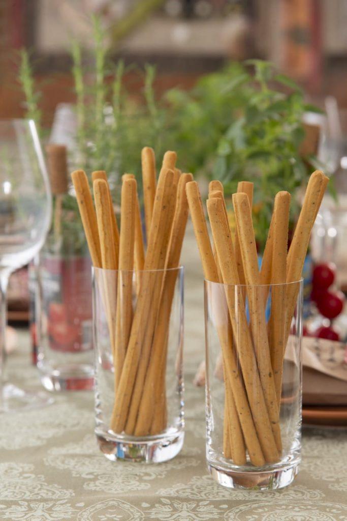 Dois copos com grissini. palitos de pão sempre servidos como aperitivo em um almoço italiano.