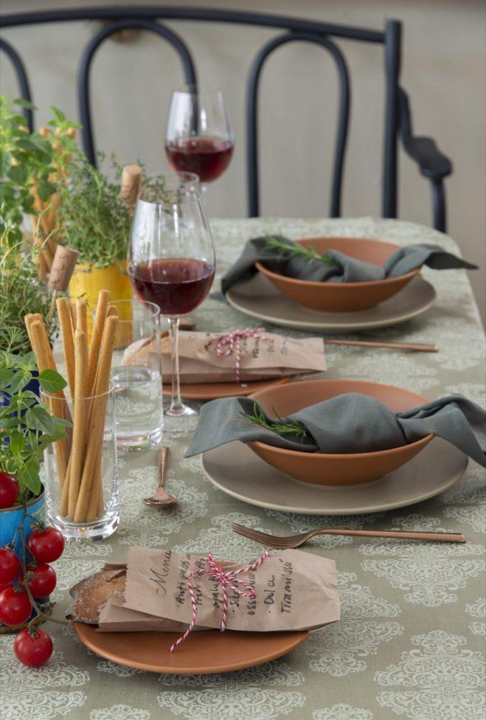 Dois lugares na mesa posta com louças em tons de marrom e verde claro.