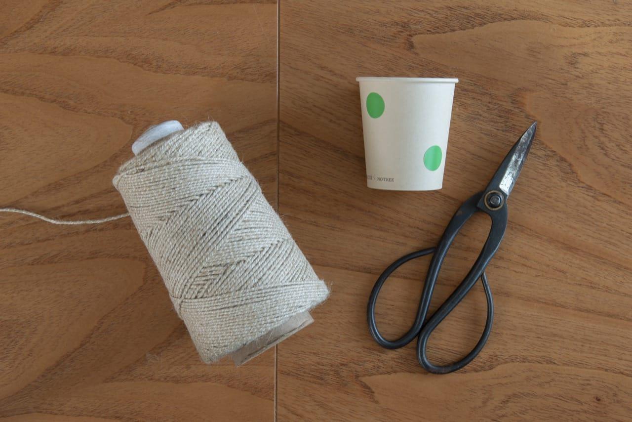 Apetrechos para fazer a cesta de barbante: rolo de barbante cru, copo descartável e tesoura.