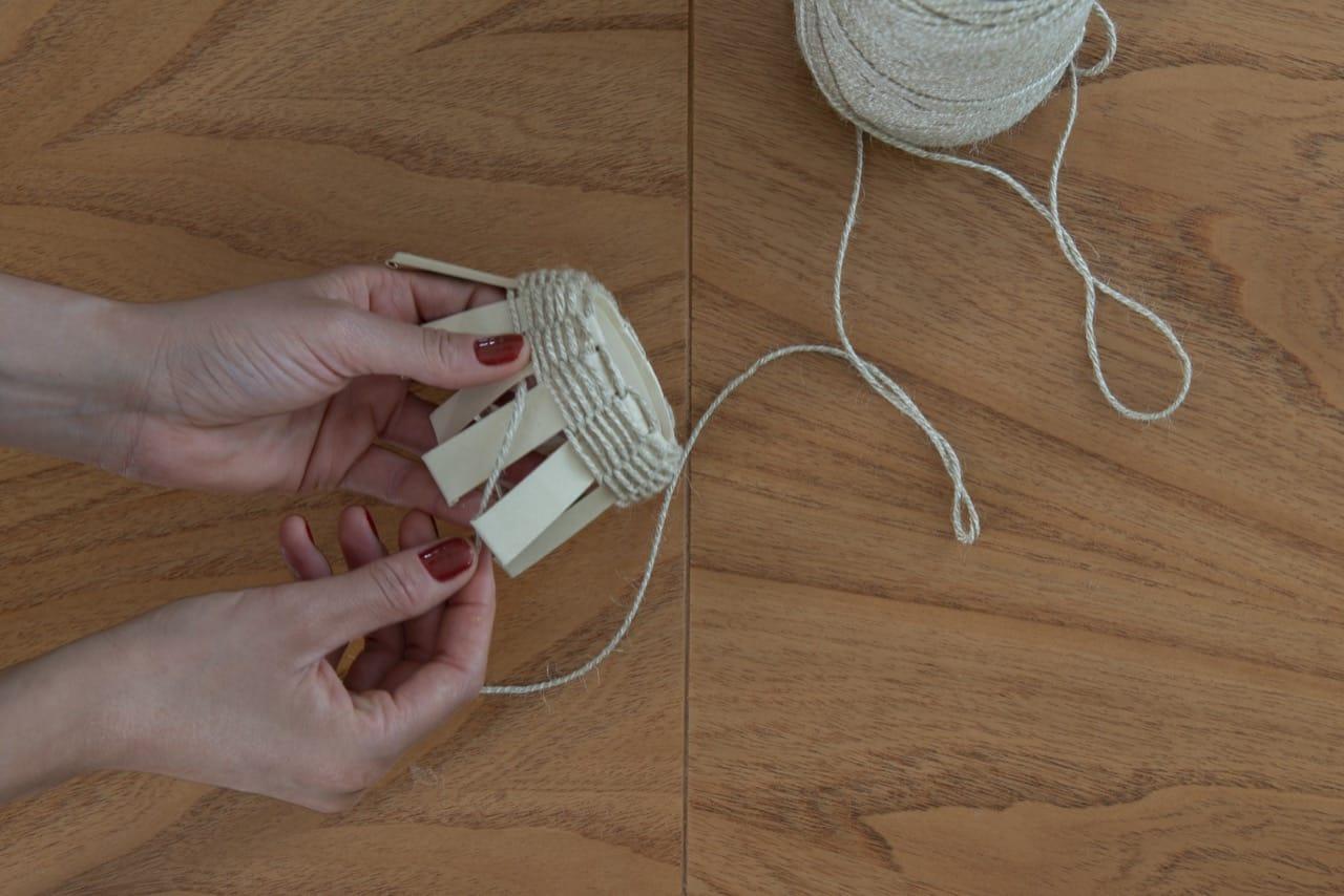 Uma mão segura o copo e outra trança o barbante entre as tiras.