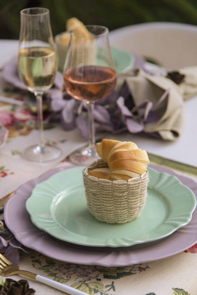 Detalhe da mesa posta: cesta com croissant sobre prato de sobremesa verde pistache, e prato raso em lilás.