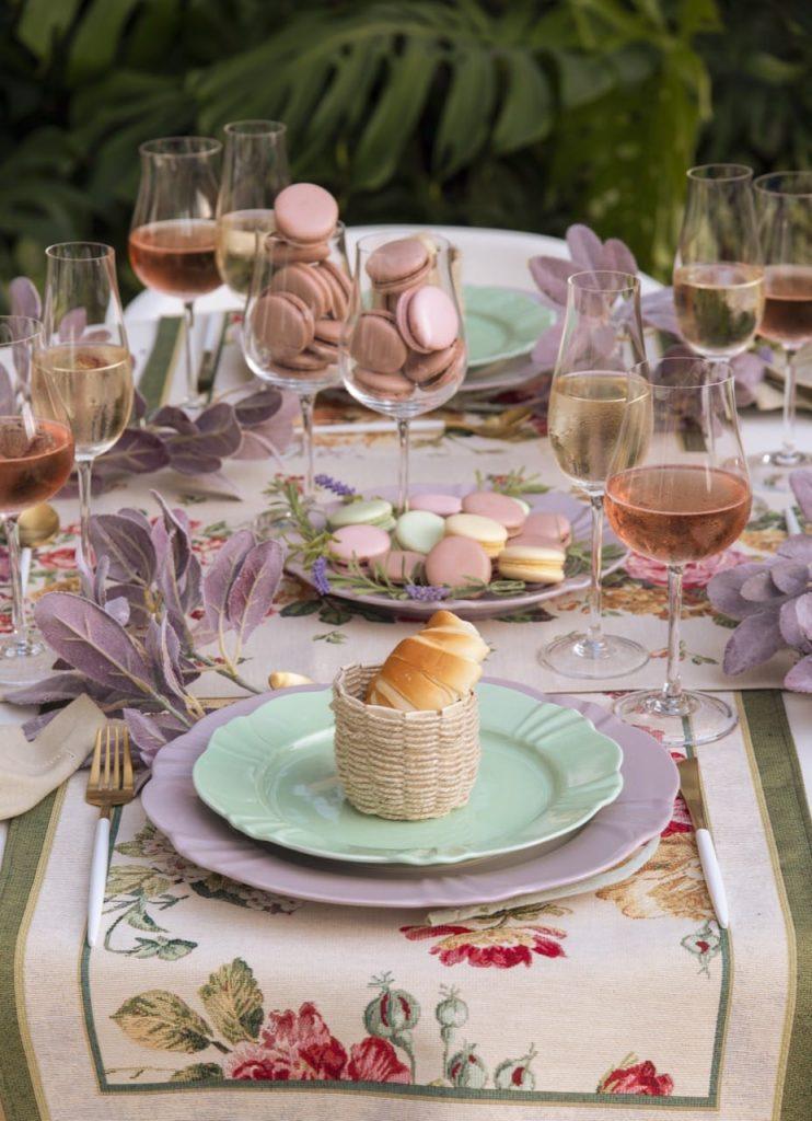 No centro da mesa posta francesa, vemos macarons em um prato e em duas taças de cristal.