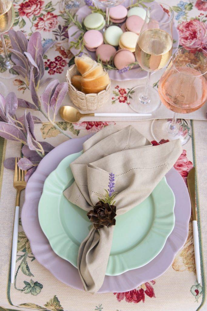 Foto feita de cima mostra um prato de sobremesa verde claro, sobre um prato raso lilás. Há um guardanapo bege sobre o primeiro prato.