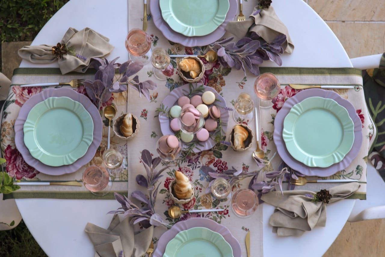 Foto feita de cima mostra uma mesa branca, redonda, com louças em tons de liás e verde claro.