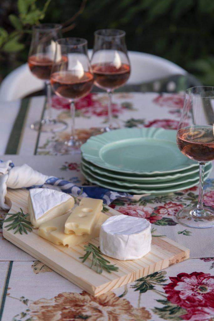 Na mesa posta francesa, temos uma tábua de madeira com três tipos de queijo: brie, camenbert e suíço.