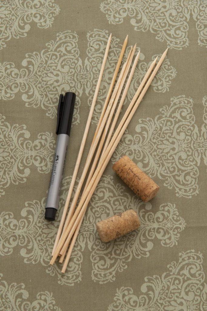 Foto feita de cima mostra uma caneta, vários palitos de madeira e duas rolhas.