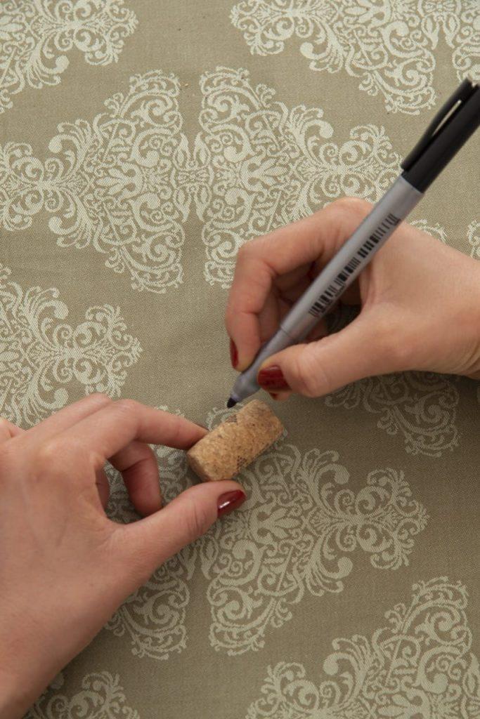 Uma mão feminina segura a rolha, e a outra segura a caneta para escrever o nome da convidada.