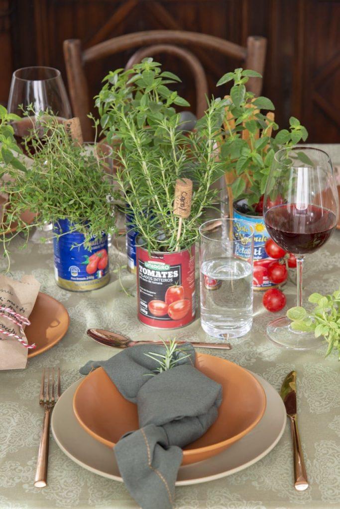 No centro da mesa, várias latas com ervas e marcadores de lugar feitos de rolha.